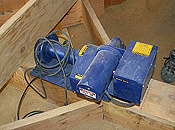 A blue machine, about the size of a breadbox, rests on wooden braces beside a person's lower leg.