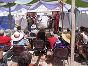 Three presenters on a raised stage speak before an audience of a few dozen burners beneath a shade structure.