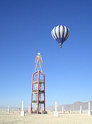 A hot air balloon hovers behind the Burning Man effigy, which stands upon a four-story, open rectagular framework.